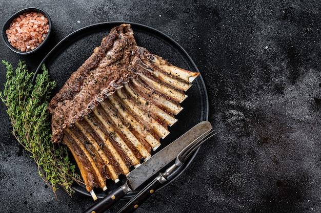 백리향과 함께 접시에 양고기 양고기 갈비 찹의 구운된 랙. 검은 배경. 평면도. 공간을 복사합니다.