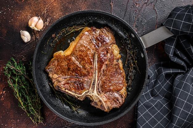 Барбекю жареное говяжье мясо на т-коне стейк с травами на тарелке на деревянном столе. вид сверху.
