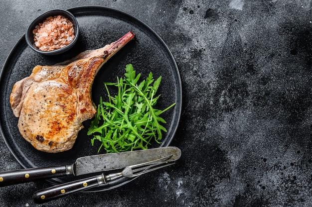 Мясной стейк из свиной отбивной из томагавка на гриле на мраморной доске