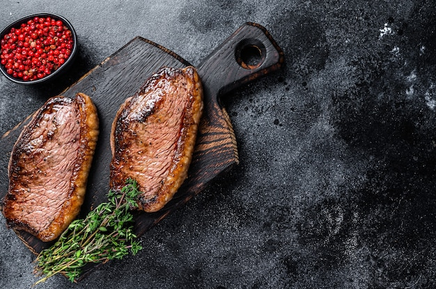 Bbq grilled top sirloin cap or picanha steak on a wooden cutting board. black background. top view. copy space.