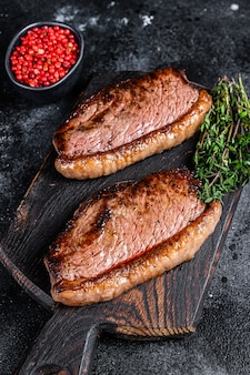 Bbq grilled top sirloin cap or picanha steak on a wooden cutting board. black background. top view.
