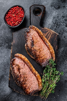 Bbq grilled top sirloin cap or picanha steak on a wooden cutting board.
