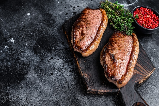 Bbq grilled top sirloin cap or picanha steak on a wooden cutting board
