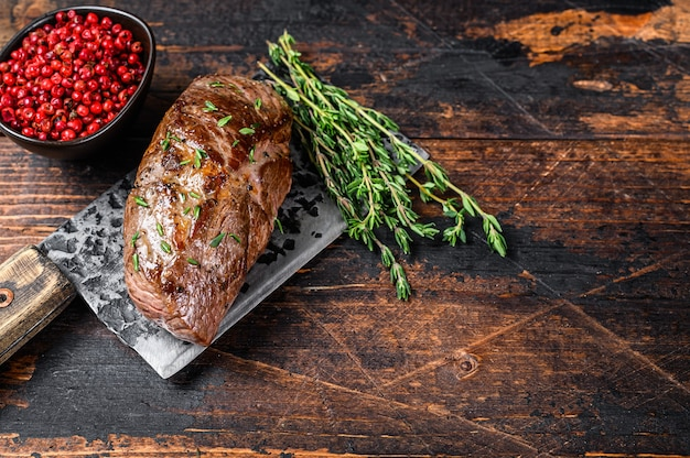 Bbq grilled veal sirloin meat steak on a meat cleaver with herbs