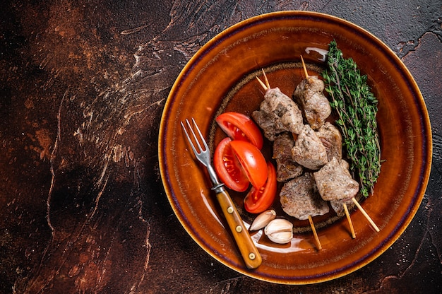 Bbq lamb meat on wooden skewers with vegetables on a rustic plate. dark background. top view. copy space.