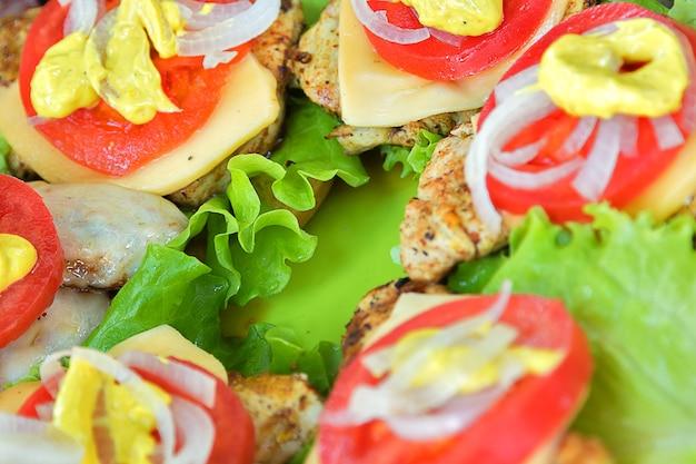 Мясо барбекю с сыром, помидорами, луком и листьями салата. на рулоне и зеленой пластиковой доске
