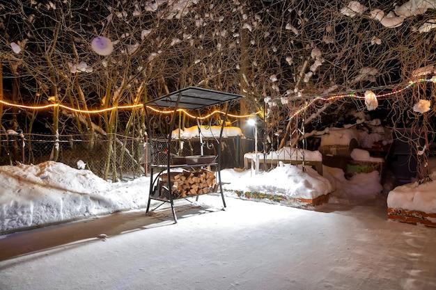 冬の家の近くでバーベキュー。夜、花輪が燃え、雪が降っています。空の遊び場。彼らは収穫した薪をグリルの下に置いた。