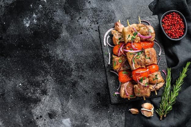 木製の串焼きにバーベキューポークとビーフケバブの肉。黒の背景。上面図。スペースをコピーします。