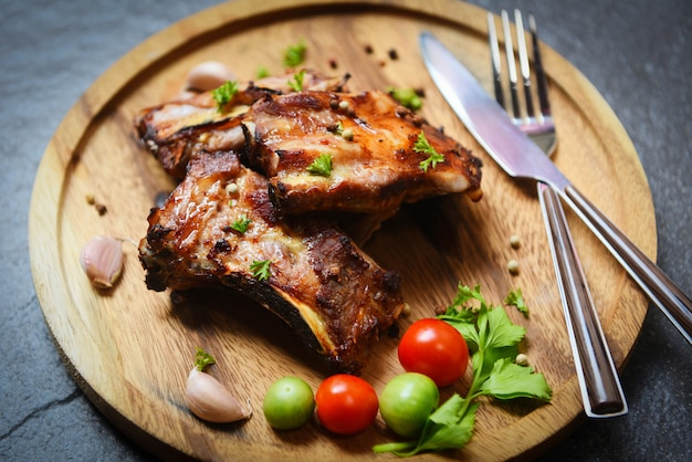 Bbq pork ribs grilled with tomatoes herbs and spices on wooden plate - roasted barbecue pork spare rib sliced