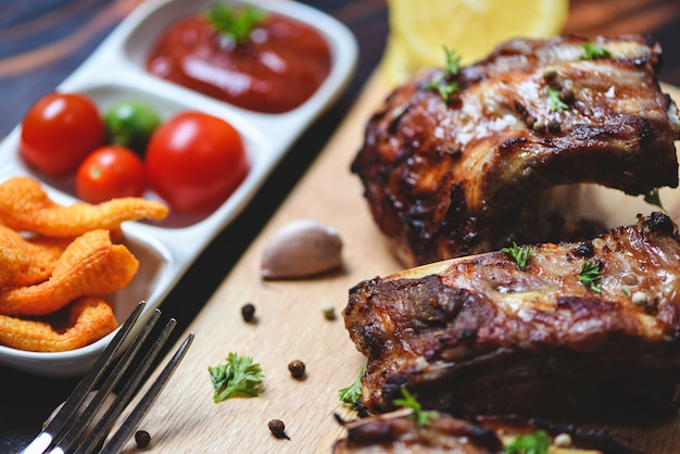 Bbq pork ribs grilled with tomatoes ketchup and herbs spices served on the table