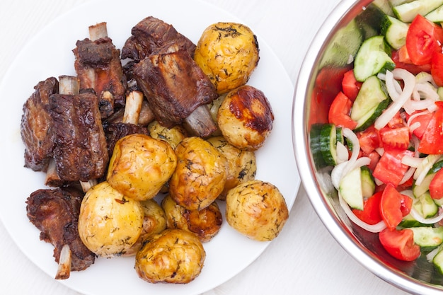 Bbq ribs with potatoes and salad with tomatoes and cucumbers