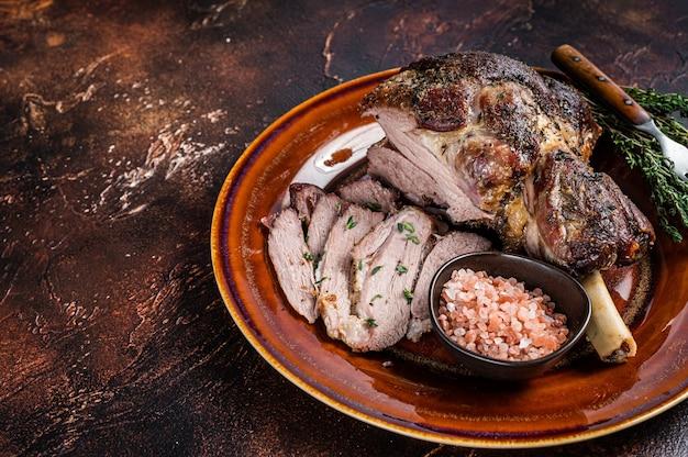 Баранья ножка bbq roast баранина, нарезанная на деревенской тарелке. темный фон. вид сверху.