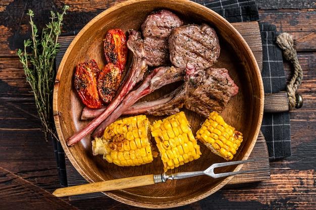 Bbq 구운된 양고기 스테이크 스테이크, 양고기 나무 접시에. 어두운 나무 배경입니다. 평면도.