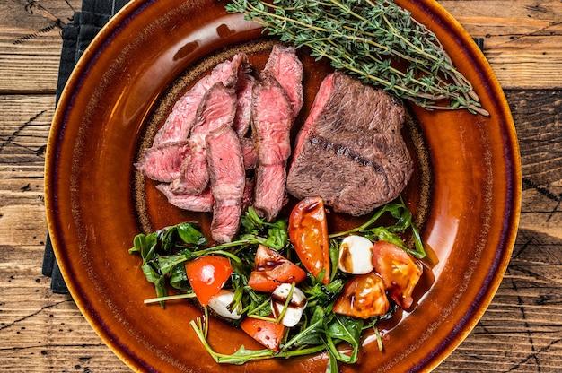 바베큐 구이 오이스터 탑 블레이드 또는 플랫 아이언 로스트 비프 고기 스테이크를 샐러드와 함께 접시에. 나무 배경입니다. 평면도.