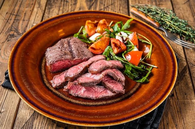 サラダ付きプレートにバーベキューローストオイスタートップブレードまたはフラットアイアンローストビーフミートステーキ。木製のテーブル。上面図。