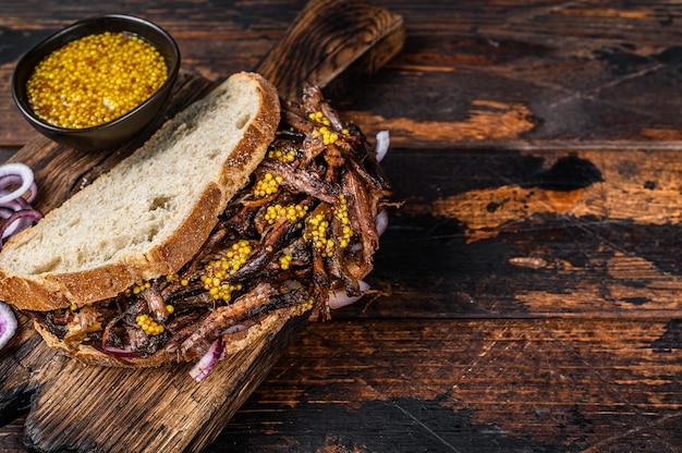 천천히 구운 풀드 돼지 고기를 곁들인 bbq 샌드위치. 어두운 나무 배경입니다. 평면도. 공간을 복사하십시오.
