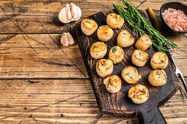 Барбекю обжаренные гребешки с масляным соусом на деревянной доске на деревянном столе. вид сверху.
