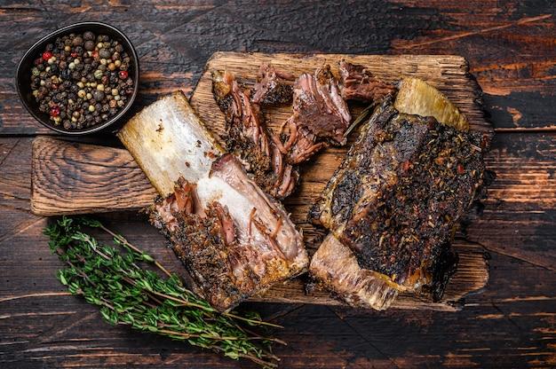 허브와 고기 칼을 곁들인 짧은 척 쇠고기 갈비 바베큐. 어두운 나무 배경입니다. 평면도.