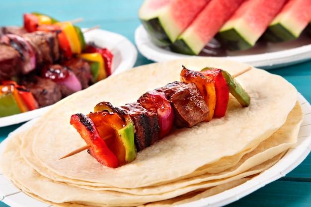 Барбекю вертел с говядиной и овощами на стол для пикника