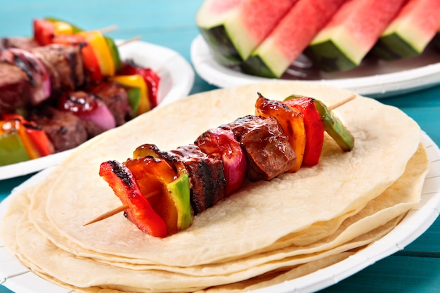 Bbq skewer with beef and vegetables on picnic table