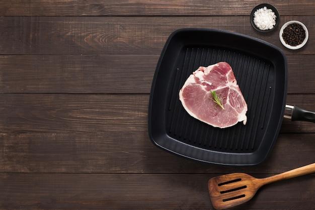 木製の背景にバーベキューステーキを設定します。テキスト用のコピースペース