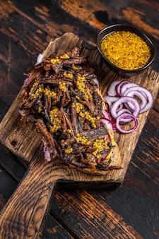 천천히 구운 양지머리 쇠고기를 곁들인 bbq 텍사스 샌드위치. 어두운 나무 배경입니다. 평면도.
