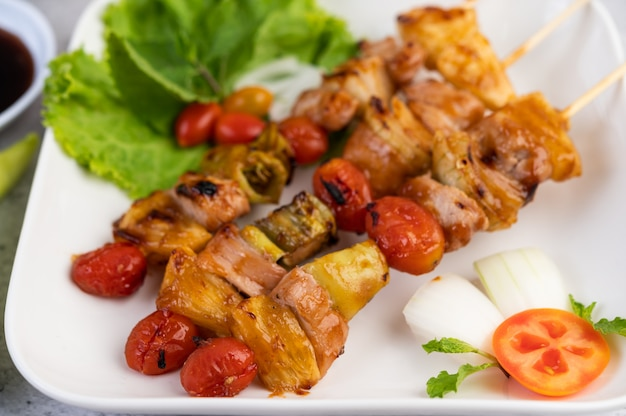 하얀 접시에 토마토와 피망을 완비 한 다양한 고기가있는 bbq.