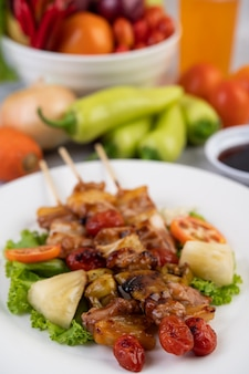 Барбекю с разнообразным мясом, в комплекте с помидорами и сладким перцем на белой тарелке.