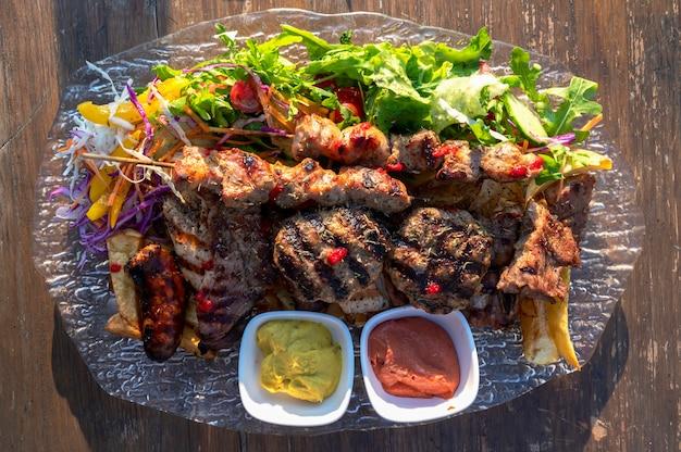 Barbecue con condimenti e salsicce su un piatto all'aperto