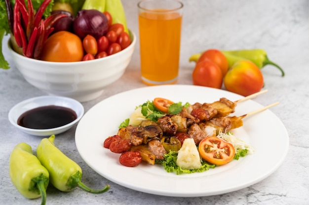 Bbq with a variety of meats, complete with tomatoes and bell peppers on a white plate.