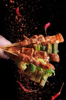 四川産唐辛子を使用したマラ焼きバーベキュー(bbq)、調味料のマラ粉と唐辛子の落下、辛くてスパイシーで美味しい屋台の食べ物。