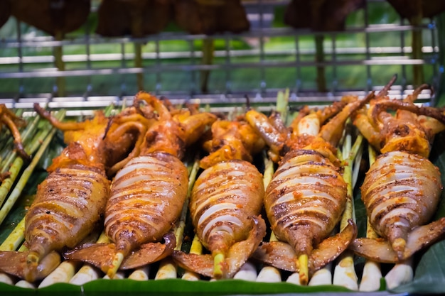 タイでグリルされたイカの通りの食べ物。 bbqイカのスティックに焼きイカの多く。