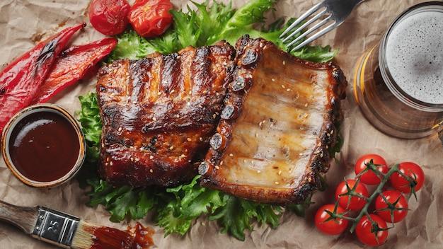 Крупный план свиных ребрышек зажарил с соусом bbq и карамелизованный в меде на бумаге.