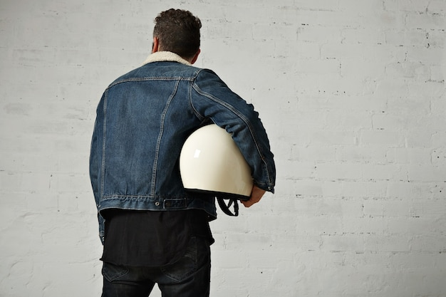 Bck view on moto biker wears shearling denim jacket and black blank henley shirt, holds vintage beige motorcycle helmet, isolated in center of white brick wall