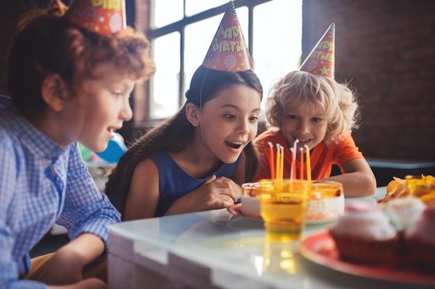 バディケーキ。 3人の子供がケーキを見て、面白がって感じ