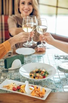誕生日。グラスワインを持って、友達と乾杯の笑顔の若い女性