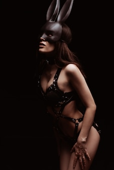 Bdsm concept. sexy girl in black leather lingerie and a mask of a bunny