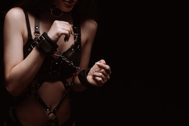 Bdsm. girl in handcuffs and sexy black leather underwear