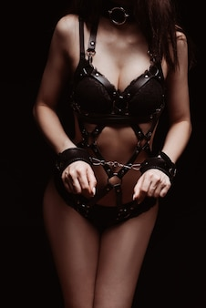 Bdsm. 수갑과 섹시한 검은 가죽 속옷 소녀