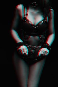 緊縛。手錠とセクシーな黒革の下着の女の子。