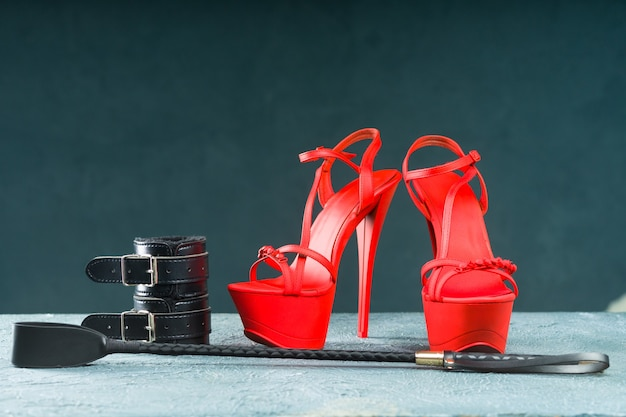 Bdsm outfit for adult sex games. red high-heeled striptease shoes and handcuffs, whip on dark background - image