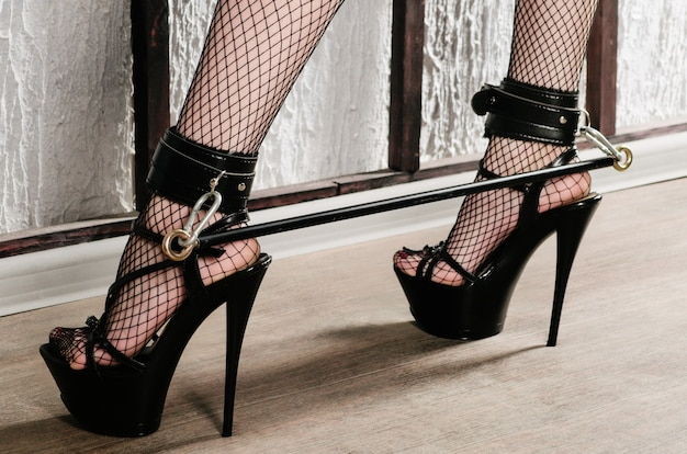 Bdsm outfit for adult sex games. women's legs in black stockings in a mesh in high heels are shackled with shackles and bandage - image