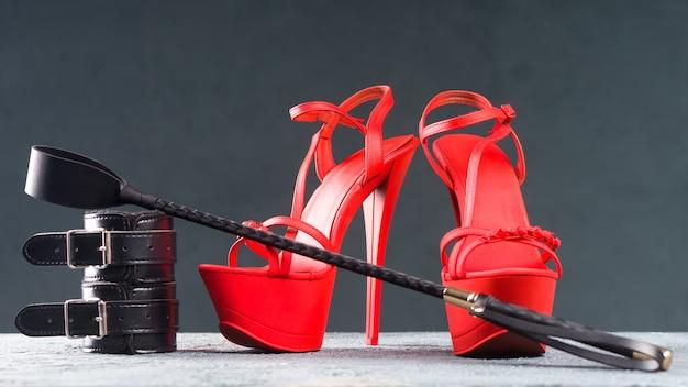 大人のセックスゲームのためのbdsmの衣装。赤いハイヒールのストリップシューズと手錠、暗い背景に鞭-画像