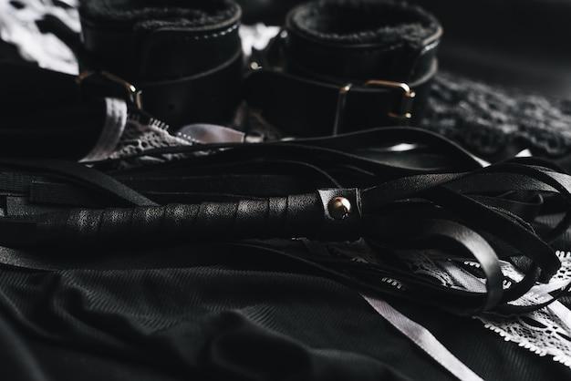 Bdsmとメイドコスチュームのための革の手錠と鞭