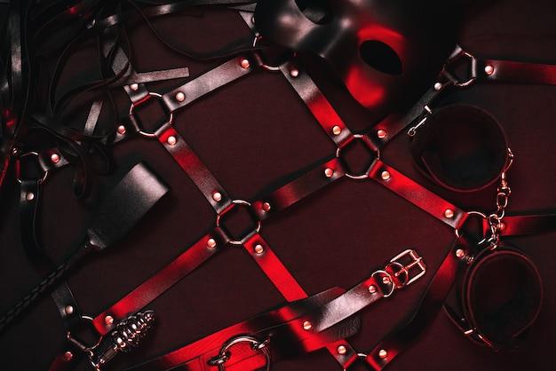 Bdsmセックスのためのセックスショップからのおもちゃのセット。フロガーのホイップ、革の手錠、チョーカー、ベルト、金属製のバットプラグ