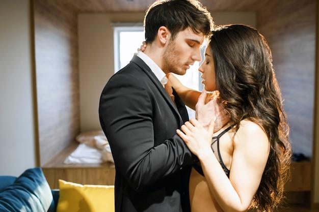 リビングルームで若いセクシーなカップル。スーツのビジネスマンは、ランジェリーの女性に触れます。情熱的な瞬間。欲望、誘惑、官能性。 bdsm、立ちポーズ。