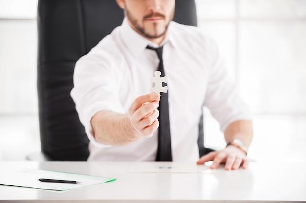 Станьте частью успешной команды! уверенный молодой человек в рубашке и галстуке показывает элемент головоломки, сидя на своем рабочем месте