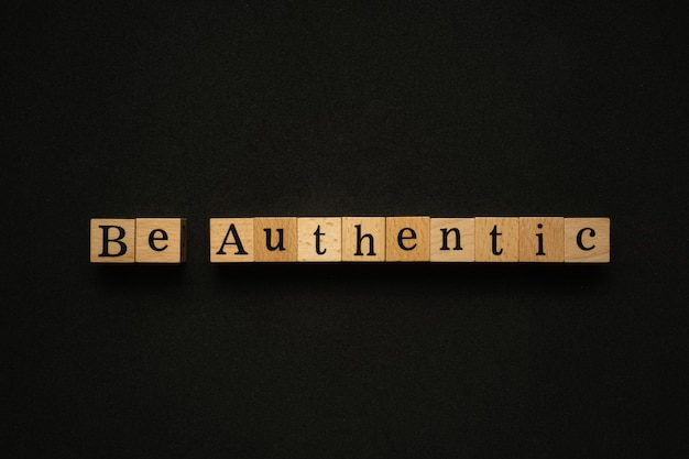 Be authentic text on wooden block.