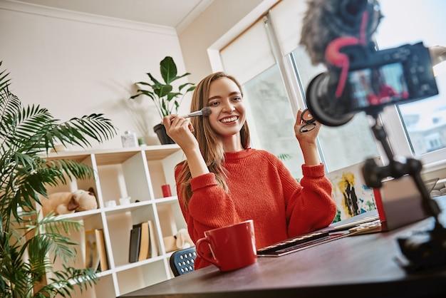 새로운 기록을 남기면서 뷰티 제품을 바르는 브러시를 사용하여 아름답고 귀엽고 젊은 블로거가 되십시오.