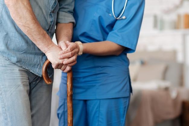 注意してください。患者を手で持ち、しっかりと立っていることを確認し、家の中を動き回るのを手伝う、アクティブで生産的な立派な女性